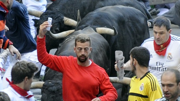 "A participant takes a ""selfie"" during the fifth bull-run of the San Fermin Festival in Pamplona, northern Spain, on July 11, 2014. (Photo credit should read RAFA RIVAS/AFP/Getty Images)"